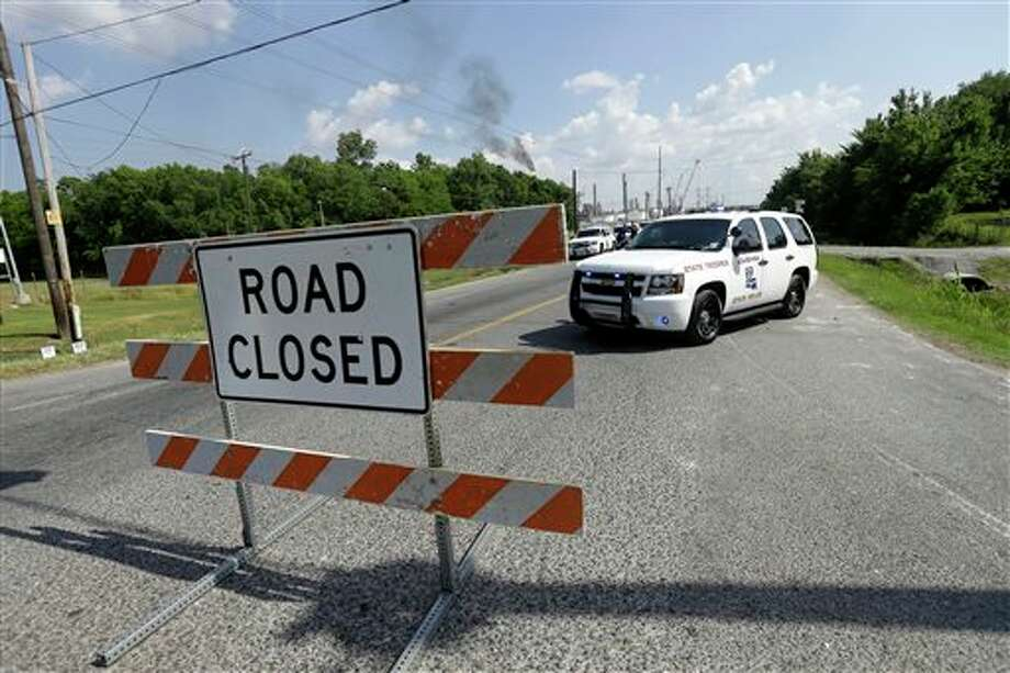 State police man a roadblock as smoke burn off from a flare at a chemical plant fire is seen about twenty miles southeast of Baton Rouge, in Geismar, La., Thursday, June 13, 2013. The plant makes highly flammable gases that are basic building blocks in the petrochemical industry. Photo: Gerald Herbert, AP / AP