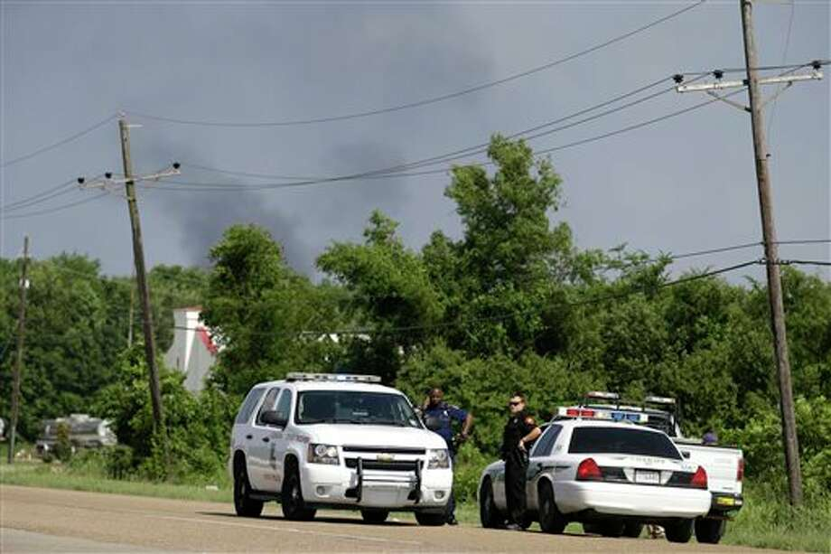 State police man a roadblock as smoke burns off from a flare at a chemical plant fire about twenty miles southeast of Baton Rouge, in Geismar, La., Thursday, June 13, 2013. The plant makes highly flammable gases that are basic building blocks in the petrochemical industry. Photo: Gerald Herbert, AP / AP