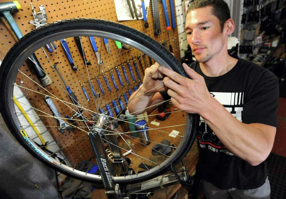 Bike mechanic Cody Madigan works on the wheel of a Specialized Tricross bike, used for cyclocross riding,  on Wednesday, June 12, 2013, at Blue Sky Bicycles in Saratoga Springs, N.Y. (Cindy Schultz / Times Union) Photo: Cindy Schultz / 00022778A