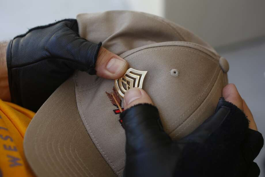 Sam Keeney pins a United States Marines pin to his hat during the first day of the Valor Games Far West in Leo J. Ryan Memorial Park in Foster City, Calif. on June 11, 2013.