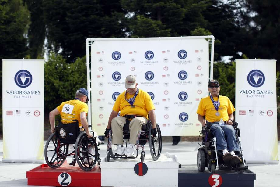 (left to right) John Grimm, Sam Keeney and Tim Daubert take their positions at the podiums after placing in seated archery during the first day of the Valor Games Far West in Leo J. Ryan Memorial Park in Foster City, Calif. on June 11, 2013.