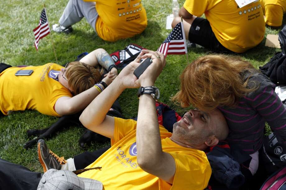 Kenny Roman is kissed by his wife Altagracia Roman while taking a break from archery during the first day of the Valor Games Far West in Leo J. Ryan Memorial Park in Foster City, Calif. on June 11, 2013.