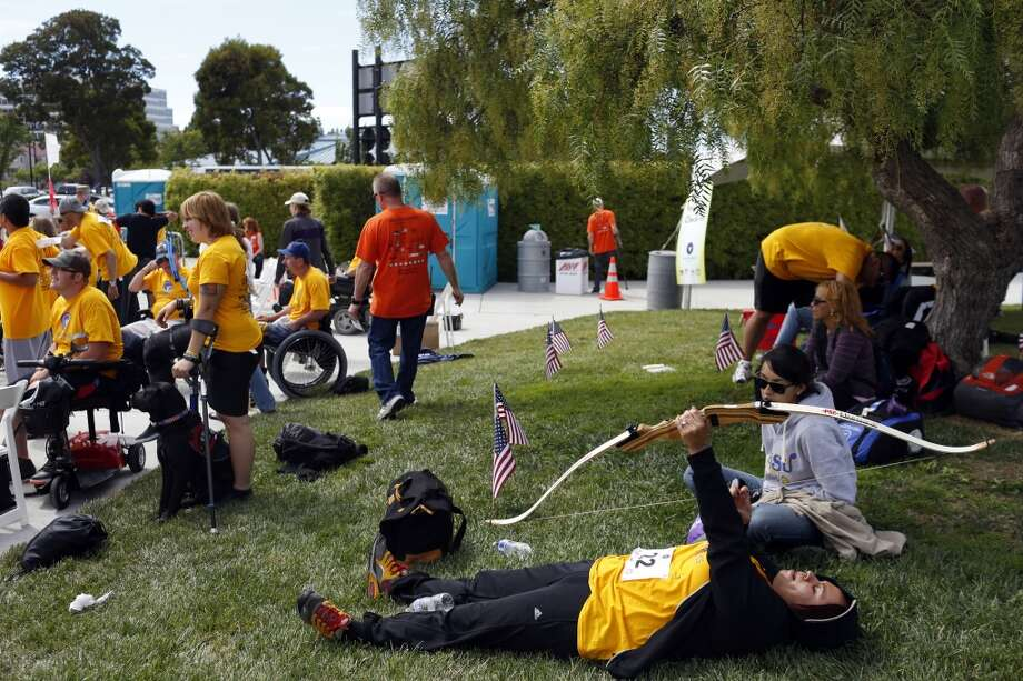 Nadine Cortez, bottom right, practices pulling the string of her bow during the first day of the Valor Games Far West in Leo J. Ryan Memorial Park in Foster City, Calif. on June 11, 2013.