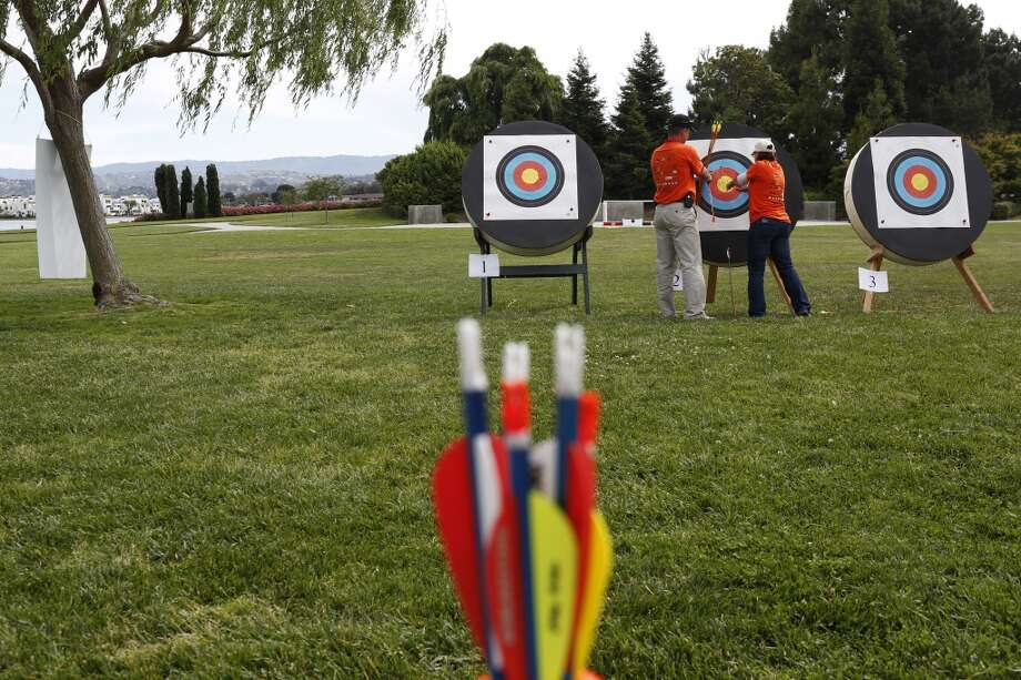 Volunteers help pull out arrows shot by wounded veterans during the first day of the Valor Games Far West in Leo J. Ryan Memorial Park in Foster City, Calif. on June 11, 2013.