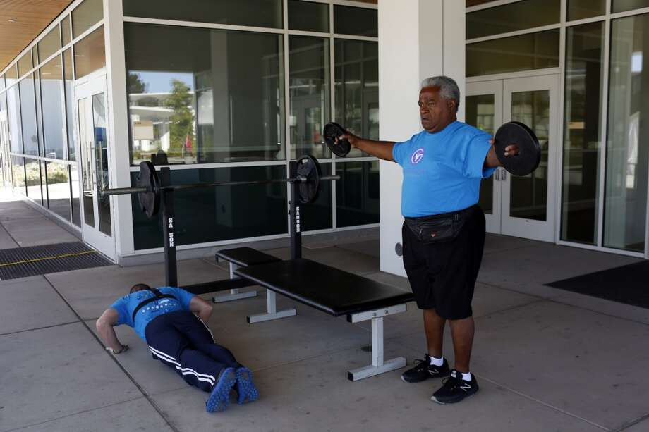 James J. Chretian Sr., right, warms up before powerlifting during the second day of the Valor Games Far West at San Mateo College in San Mateo, Calif. on June 12, 2013.