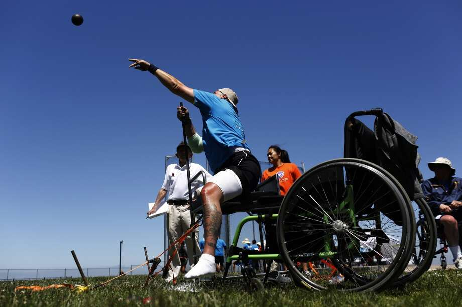 Navy Petty Officer Second Class Jonathan Moore throws a shot put during the seated shot put competition during the second day of the Valor Games Far West at San Mateo College in San Mateo, Calif. on June 12, 2013.