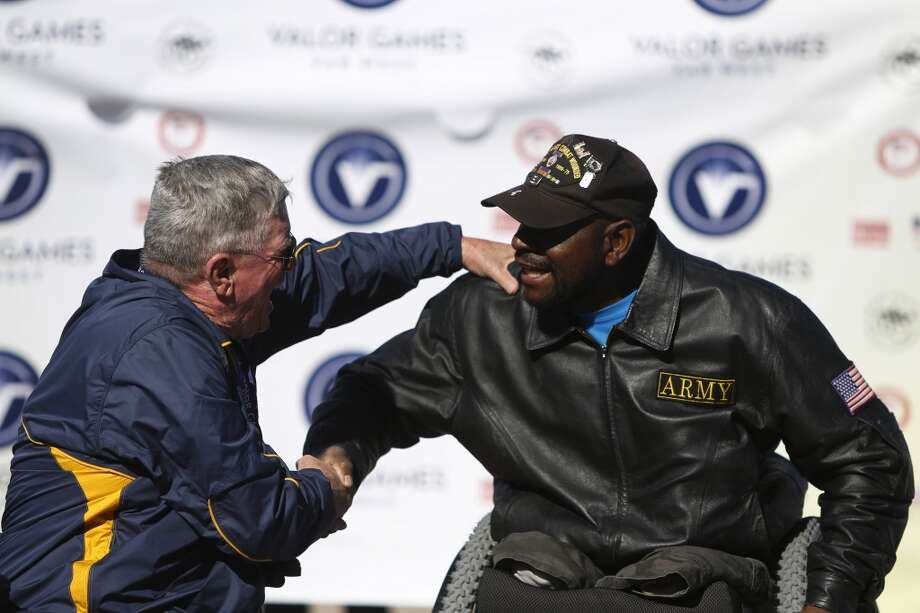 John Grimm, left, congratulates Johnnie Alexander on his first place win during the second day of the Valor Games Far West at San Mateo College in San Mateo, Calif. on June 12, 2013.
