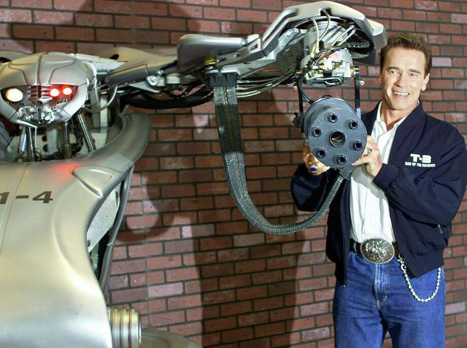 "Arnold Schwarzenegger poses for photographers with a model of an early Terminator in Mexico City July 24 2003, while promoting ""Terminator 3."" Photo: ALFREDO ESTRELLA, AFP/Getty Images / 2003 AFP"