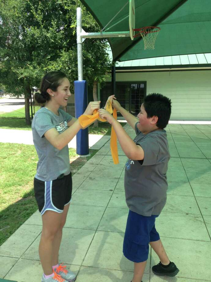 Trainer Amanda Delgado (left) uses resistance bands to do strength training exercises with 10-year-old Carlos De La Garza, who has autism, during a recent session of the Any Body Can program at the Braundera Family YMCA. Photo: San Antonio Express-News