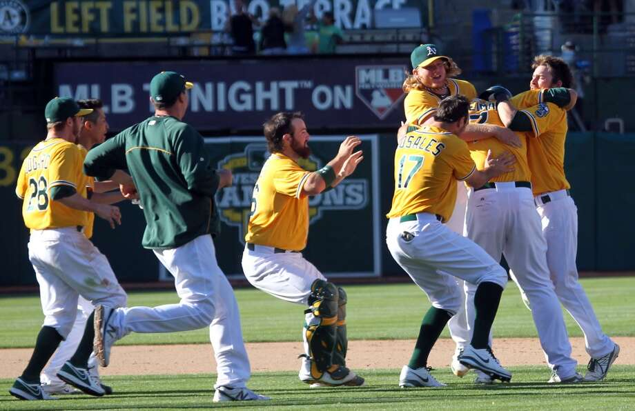 Oakland Athletics' Nate Freiman (7) celebrates with his teammates after his walk-off base hit that scored the winning run in the 18th inning against the New York Yankees Thursday, June 13, 2013, in Oakland, Calif.