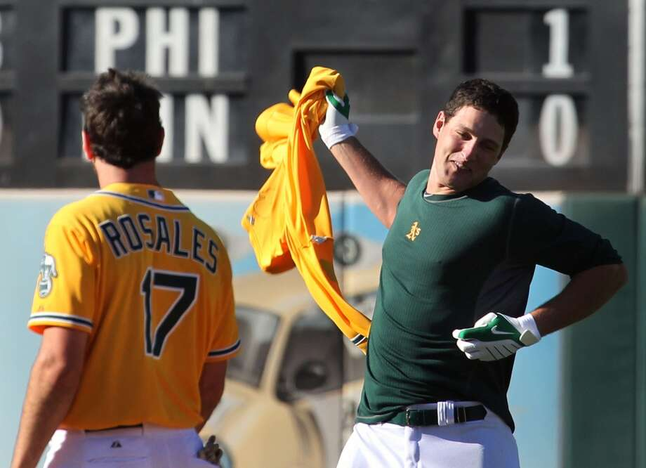 Oakland Athletics' Nate Freiman (7) right throws down his jersey after his teammates stripped it off his back in celebration of his walk-off base hit that scored the winning run in the 18th inning against the New York Yankees Thursday, June 13, 2013, in Oakland, Calif.