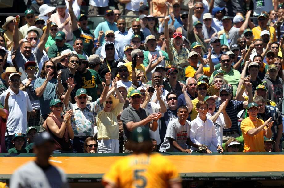 Oakland Athletics' fans celebrate John Jaso (5) score off a hit by Seth Smith in the third inning of their MLB baseball game with the New York Yankees Thursday, June 13, 2013, in Oakland, Calif.