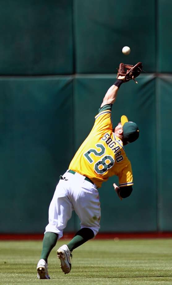 Oakland Athletics' second baseman Eric Sogard catches New York Yankee Kevin Youkils' fly ball in the 10th inning of their MLB  baseball game Thursday, June 13, 2013, in Oakland, Calif. Oakland won 3-2 in the 18th inning.