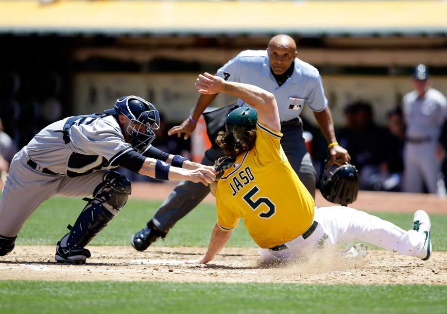 John Jaso slides safely under the tag of Chris Stewart of the New York Yankees to score on a hit by Seth Smith in the third inning.