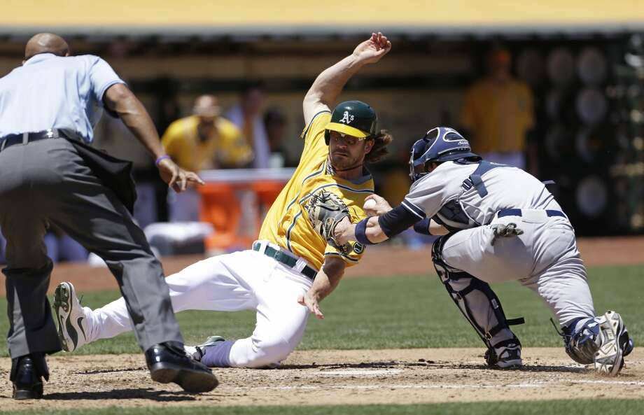 Oakland Athletics' John Jaso, center, slides into home plate to score the A's second run as New York Yankees catcher Chris Stewart, right, makes a late tag.