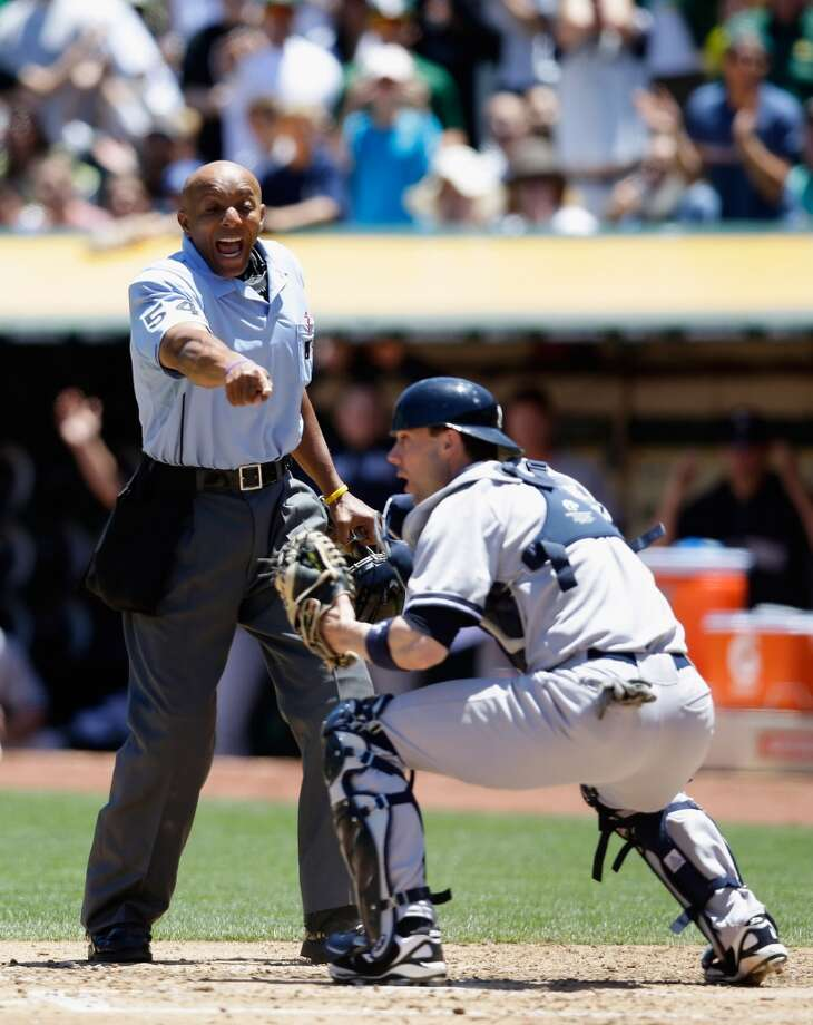 Home plate umpire CB Bucknor points to the glove of catcher Chris Stewart after John Jaso slides safely under the tag.