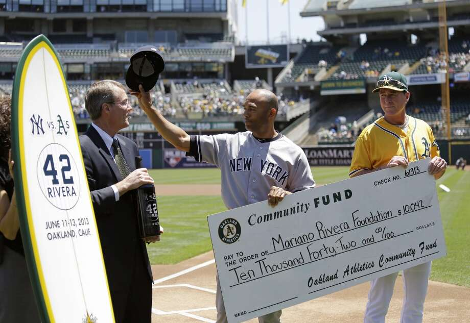New York Yankees relief pitcher Mariano Rivera, center, waves to the Oakland Athletics dugout after he was presented with farewell gifts from A's president Michael Crowley, left, and manager Bob Melvin, right, before the start of a baseball game Thursday, June 13, 2013 in Oakland, Calif. The gifts included wine, a surfboard and a donation to his foundation.