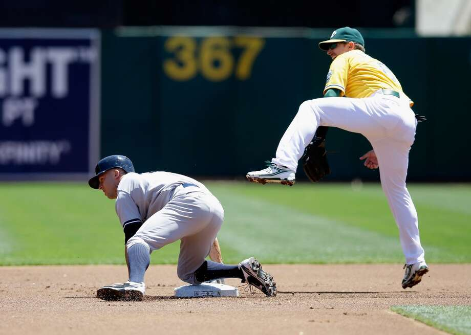 Brett Gardner of the New York Yankees slides safely past Jed Lowrie for a lead off double in the first inning at O.co Coliseum on June 13, 2013 in Oakland, California.