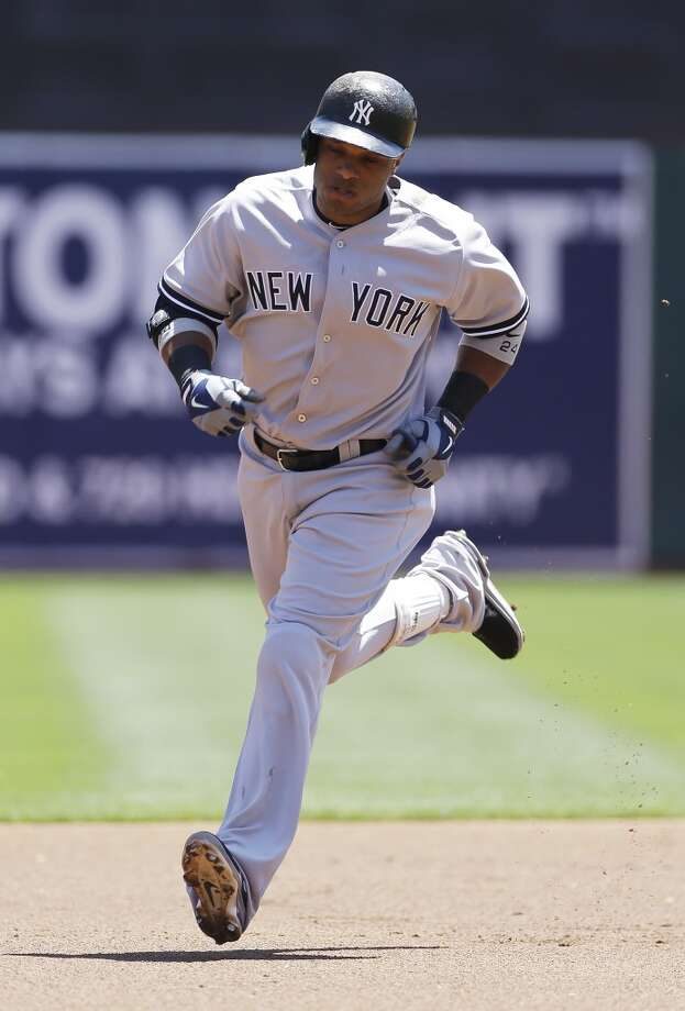 New York Yankees' Robinson Cano circles the bases after hitting a two-run homer off Oakland Athletics starting pitcher Jarrod Parker during the first inning of their baseball game June 13, 2013 in Oakland, Calif.