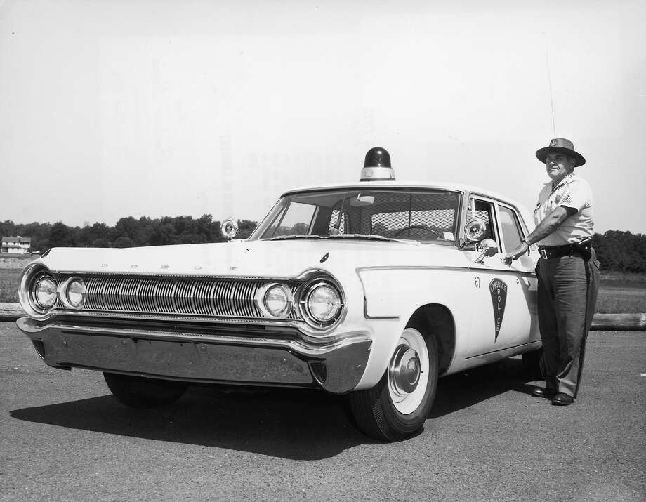 1963:  A uniformed police officer poses while opening the door of his patrol car, a Dodge sedan Photo: Harold M. Lambert, Getty Images / Archive Photos