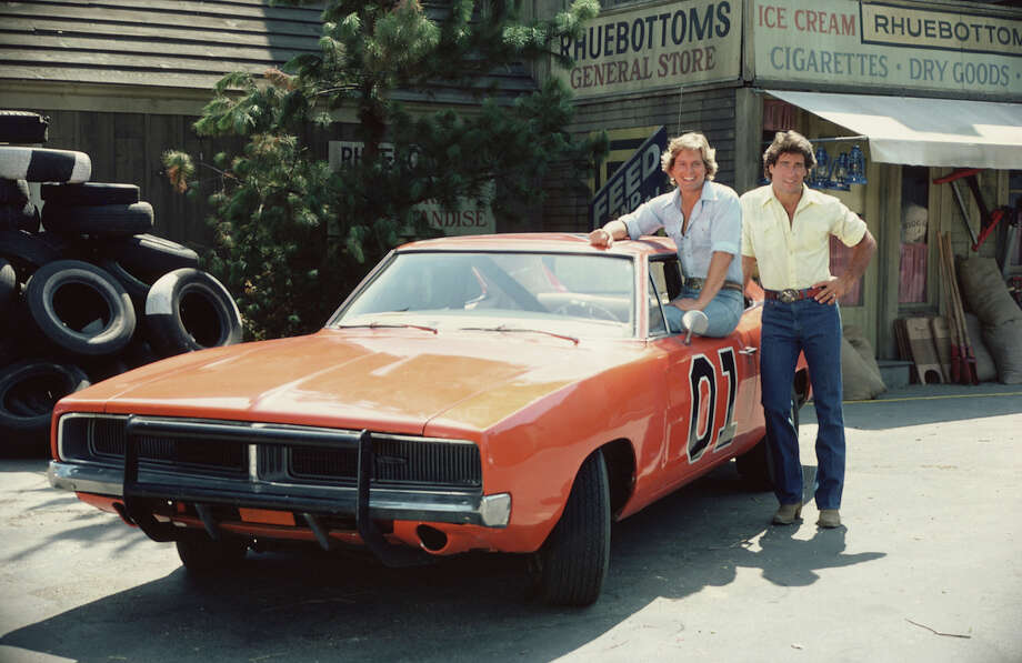1982:  Byron Cherry sits in the window of the 'General Lee,' the famous orange Dodge Charger from the television series 'The Dukes of Hazzard,' August 1982. Christopher Mayer stands next to him. Photo: CBS Photo Archive, Getty Images / 2005 CBS WORLDWIDE INC.