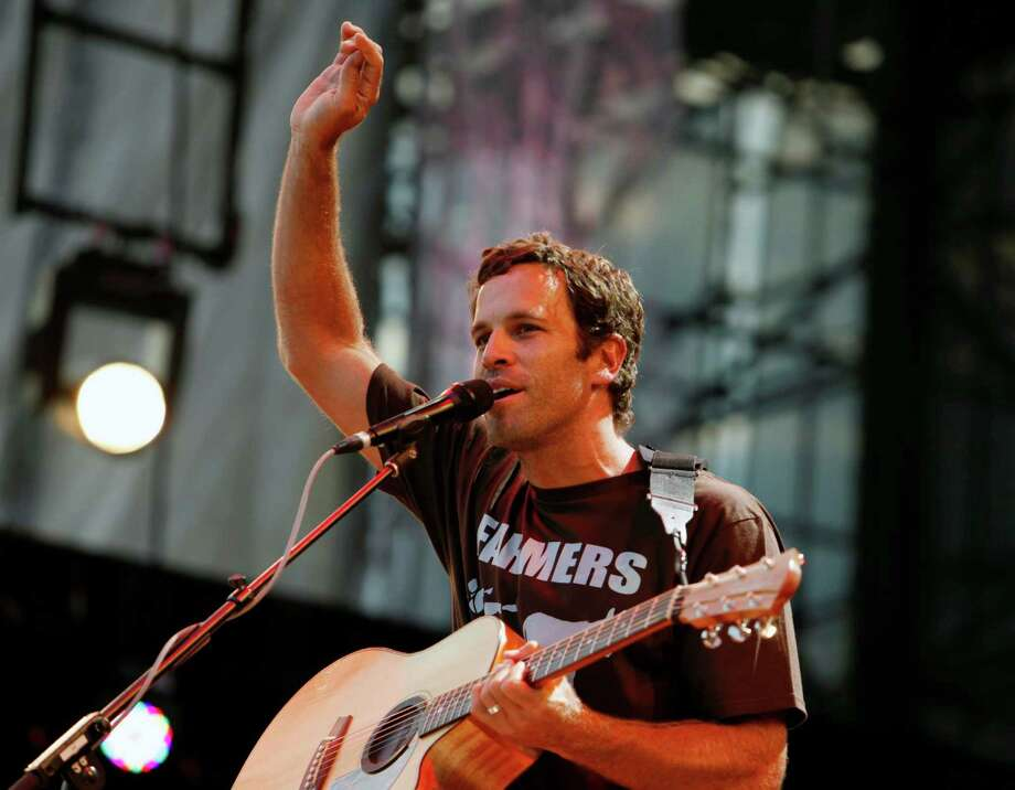 "FILE - This Sept. 22, 2012 file photo shows Jack Johnson performing during the Farm Aid 2012 concert at Hersheypark Stadium in Hershey, Pa. Johnson has agreed to take the Saturday night headlining slot at the Bonnaroo Music & Arts Festival after Mumford & Sons were forced to cancel due to bassist Ted Dwane's illness. Festival officials announced the move Friday morning. The ""Upside Down"" singer last headlined at Bonnaroo in 2008. (AP Photo/Jacqueline Larma, file) Photo: Jacqueline Larma"