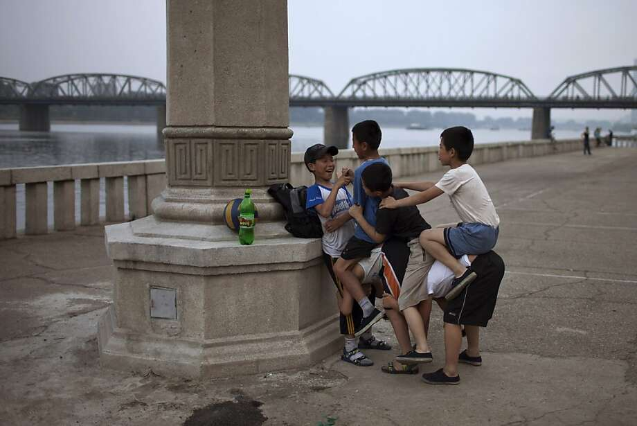 "Ride em, cowboys:North Korean kids play a game called ""horse riding"" along the bank of the Taedong River in Pyongyang. Guess who's the horse. Photo: Alexander Yuan, Associated Press"