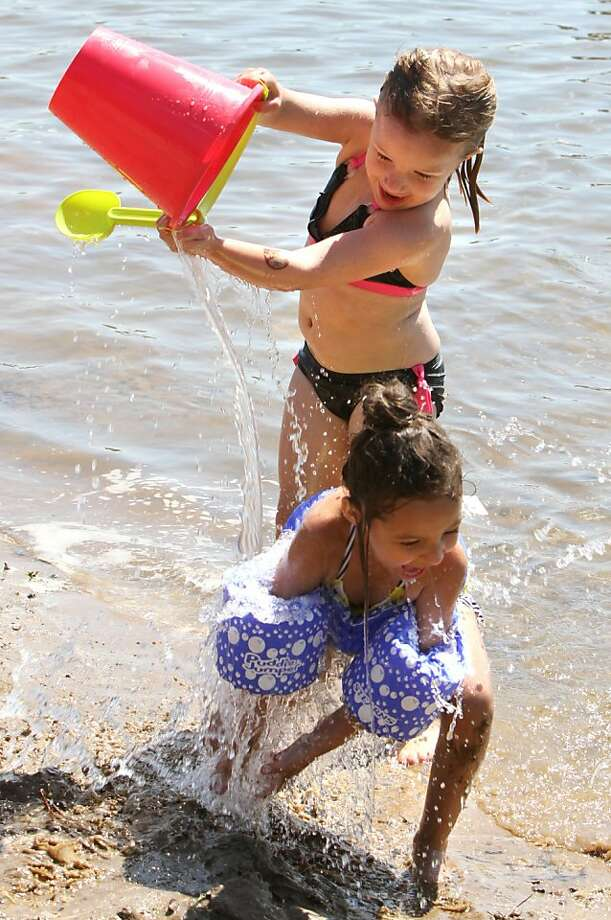 That's pretty harsh, Mello: Auria Mello ambushes her unsuspecting friend, Lola Worms, at Whipple Beach in Baxter, Minn. Photo: Kelly Humphrey, Associated Press