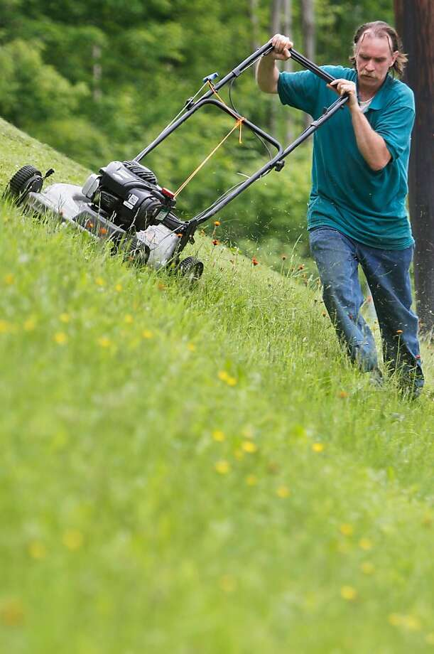 "Mowing lawns on a humid day is no fun. Mowing lawns on a 40-degree angle on humid day? ""It's a killer,"" says a sweaty Robert Renfrew in Montpelier, Vt. Photo: Toby Talbot, Associated Press"