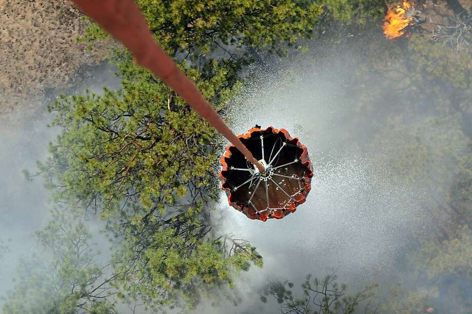 Instant rain:A bucket carried by helicopter drops a load of water in the Black Forest area northeast of Colorado Springs, Colo. As of Friday evening, the 24-square-mile wildfire had burned 400 homes, but firefighters were making headway against the blaze. Photo: Jonathan C. Thibault, Associated Press