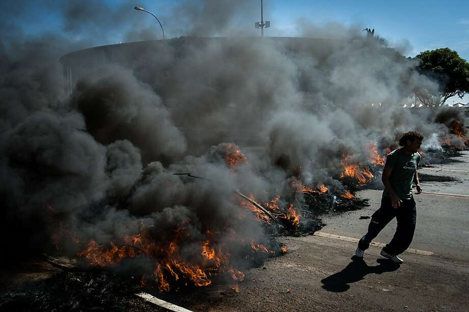 People burn tyres and block access to Brasilia's Mane Garrincha, one of the six host stadiums for the upcoming Confederations Cup, to protest in part against the government's policy of the expenditure for the 2014 FIFA World Cup, on June 14, 2013. A police spokesman said the protest was organized by the Homeless Workers Movement (MTST) which is campaigning to reduce Brazil's housing shortage by staging squatters' occupations in abandoned government buildings. Brazil faces Japan Saturday at Mane Garrincha in the opening game of the two-week Confederations Cup, a dry run for next year's World Cup.  AFP PHOTO / YASUYOSHI CHIBAYASUYOSHI CHIBA/AFP/Getty Images Photo: Yasuyoshi Chiba, AFP/Getty Images