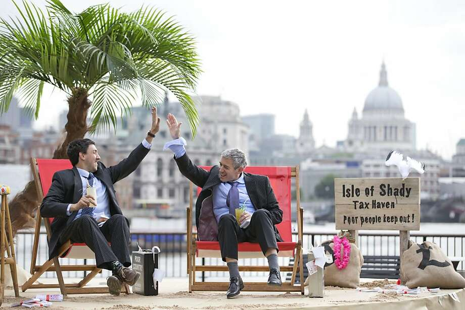 "Give me tax shelter:High-fiving fat cats enjoy drinks on the ""Isle of Shady Tax Haven"" in London. The Thames beach scene was set up by Brits calling for a crackdown on tax havens ahead of the G8 summit Monday and Tuesday in Northern Ireland. Photo: Justin Tallis, AFP/Getty Images"