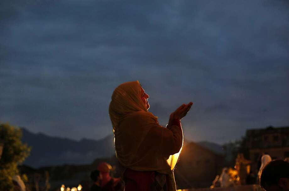 Pre-dawn devotions: A Kashmiri Muslim woman prays early in the morning at Hazratbal shrine in Srinagar. She was taking part in a ceremony held a week after Mehraj-u-Alam, which marks the ascension of Prophet Mohammed to Heaven. Photo: Dar Yasin, Associated Press