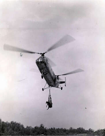 """A helicopter is bringing out a cow in a net. Crews became entangled and this method was abandoned for """"tied feet upside-down"""" method."""