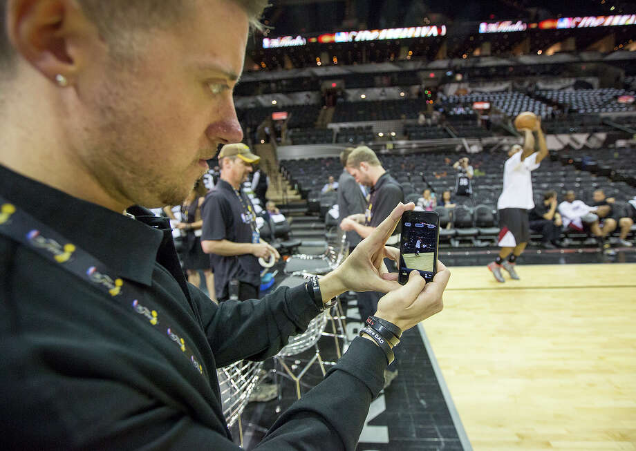 FOR BUSINESS - Jim Poorten, senior specialist of social media at the NBA, takes a photo of the pregame between the San Antonio Spurs and the Miami Heat at the AT&T Center on Thursday, June 13, 2013. MICHAEL MILLER / FOR THE EXPRESS-NEWS Photo: Michael Miller, For The Express-News / For the Express-News