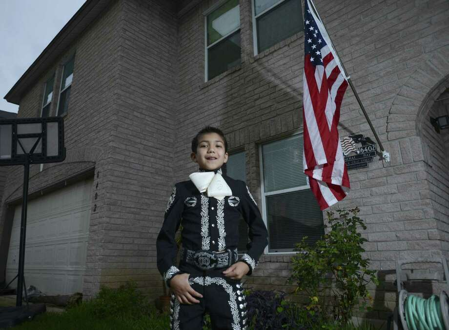 "Sebastien De La Cruz, the young mariachi who sang the ""Star Spangled Banner"" before the Spurs-Heat games on Tuesday and Thursday, stands in front of his home, smiling proudly, a day after Game 3. Sebastien was the target of racist remarks on the Internet. One of our readers defends the youth and criticizes those who sought to demean him. Photo: Billy Calzada, San Antonio Express-News"