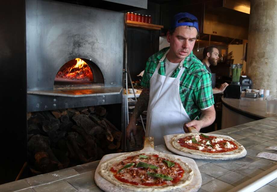 Troy (no last name given) the pizza chef works on a sausage pizza at the Forge.