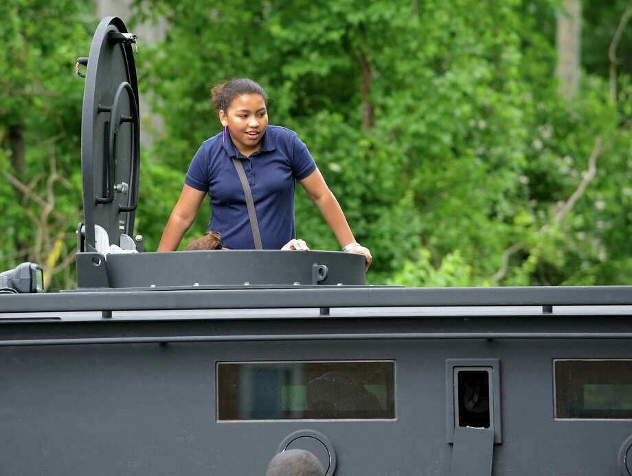 Sixth grader Monica Nieves looks up through the turret of the Bridgeport Police Department's Bearcat, an armored vehicle that was at Wilbur Cross School in Bridgeport, Conn. as part of the June Jamboree on Friday, June 14, 2013. The jamboree is a way to reward students who have demonstrated the characteristics of responsibility, respectfulness and leadership throughout the academic year. Photo: Cathy Zuraw / Connecticut Post
