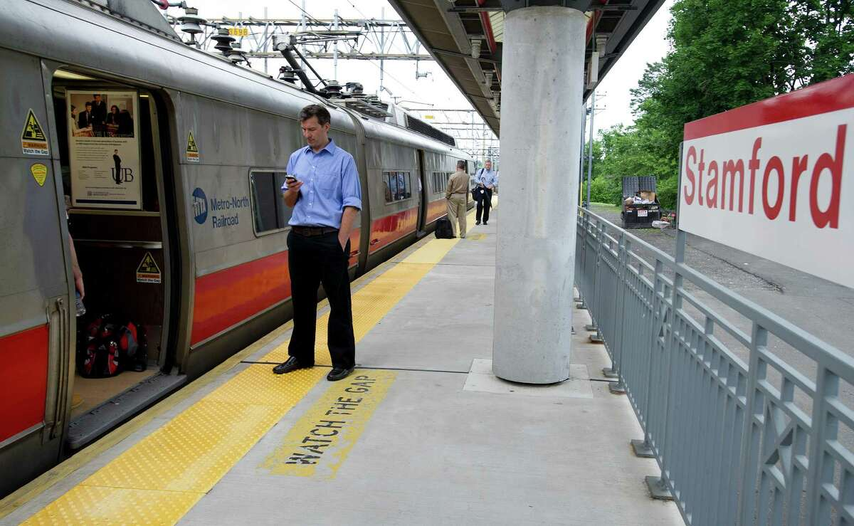 Passengers stand on the platform at Stamford's train station as their east-bound train waits for a rail bridge in Norwalk to be repaired after it was stuck in the up position on Friday, June 14, 2013.