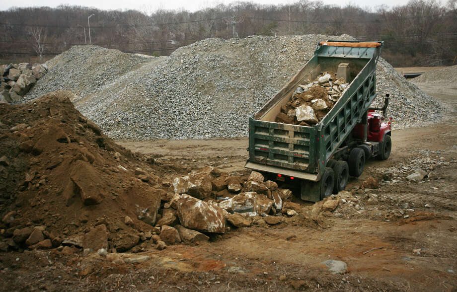 A truckload of large rocks is dumped on Mark IV Construction's property at 1234 Huntington Turnpike in Bridgeport on Wednesday, February 15, 2012. Photo: Brian A. Pounds / Connecticut Post