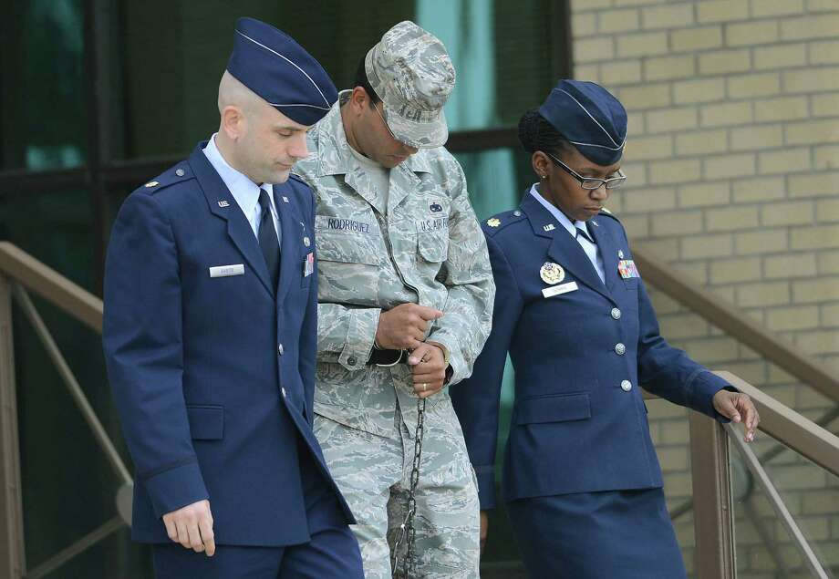 Air Force Tech Sergeant Jaime Rodriguez, middle, exits the court at Lackland Air Force Base where he was sentenced for sex crimes on Friday, June 14, 2013. Photo: Billy Calzada, San Antonio Express-News / San Antonio Express-News