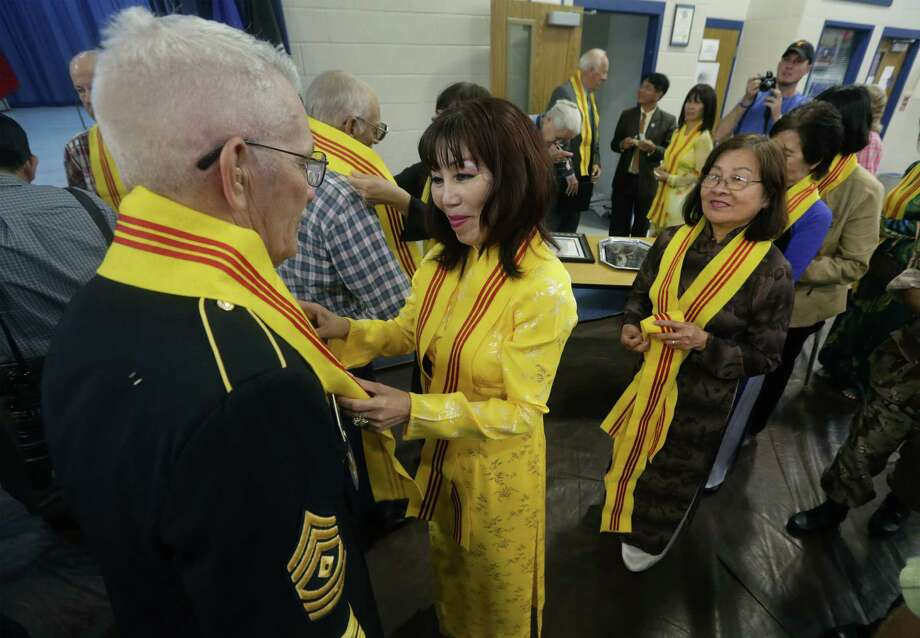 Elizabeth Hoang, center, of the Vietnamese Texas Women Association, places a sash on Vietnam veteran Fred Hudgeons, left, of Austin as veterans from both the U.S. and Vietnam take part in the Medina County Flag Day Ceremony, on Friday, June 14, 2013 at Natalia High School. Photo: Bob Owen, San Antonio Express-News / © 2012 San Antonio Express-News