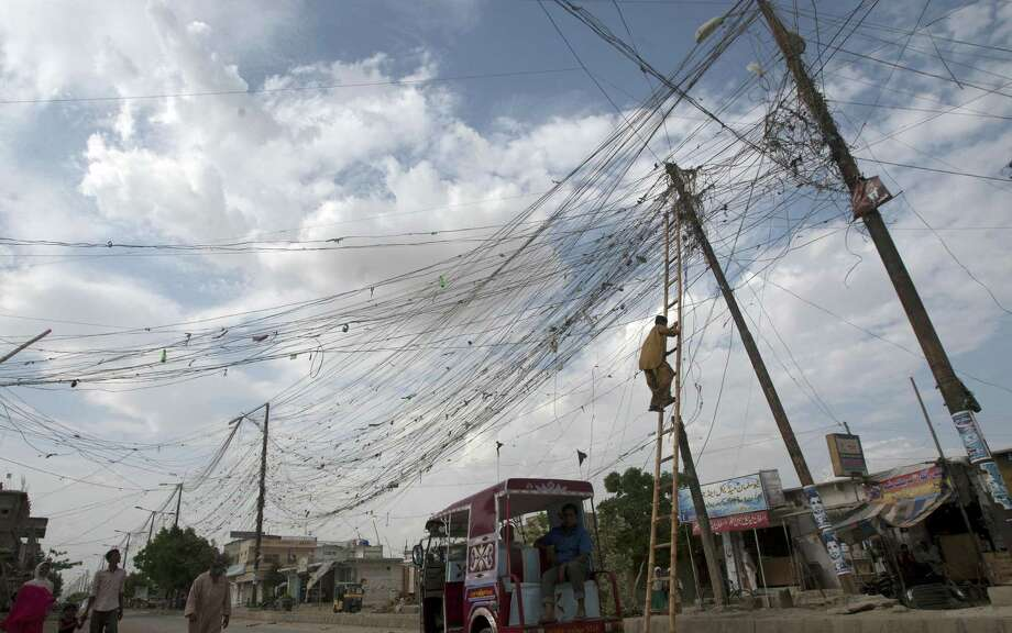 A resident climbs on a pole to adjust an illegal power connection from the transmission line on the outskirts of Karachi.  Power outages have become a way of life in Pakistan. Photo: Photos By Associated Press