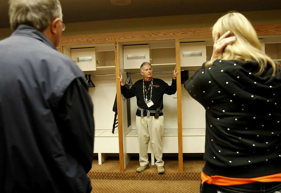 Bill Wolff leads a tour group through the visitors' locker room at AT&T Park. Wolff began leading tours in 2002, years after retiring as an executive with Saks Fifth Avenue. The home locker room is off-limits, since Giants players regularly use it to work out or treat injuries. Photo: Brant Ward, The Chronicle