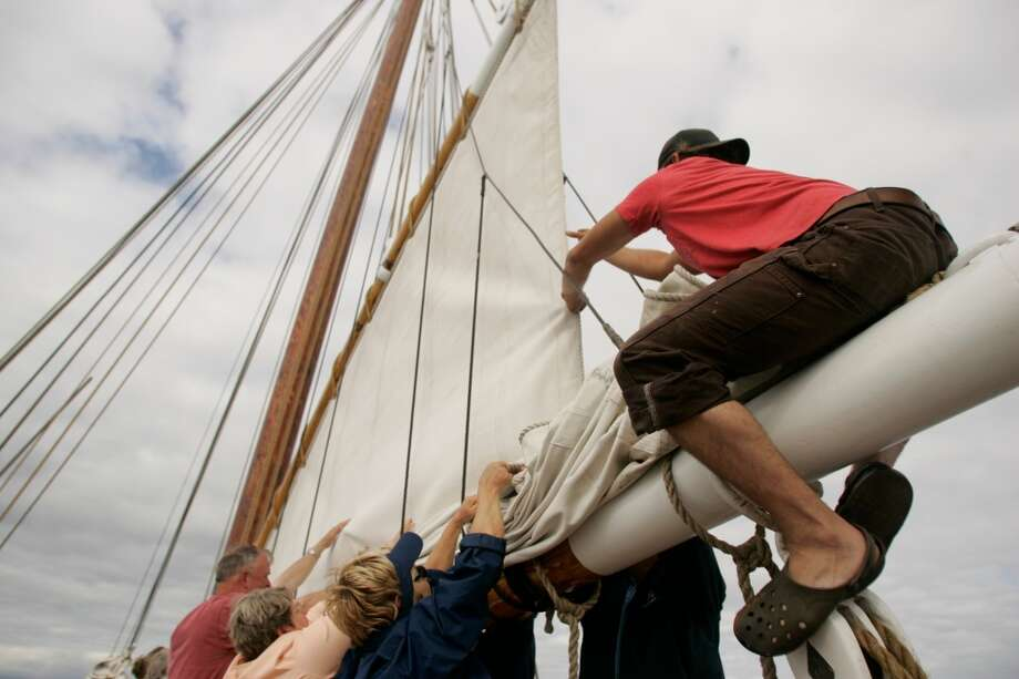 Crew and passengers lower a sail aboard the Grace Bailey.