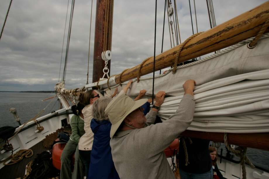 Passengers aboard the Grace Bailey help fold the main sail.