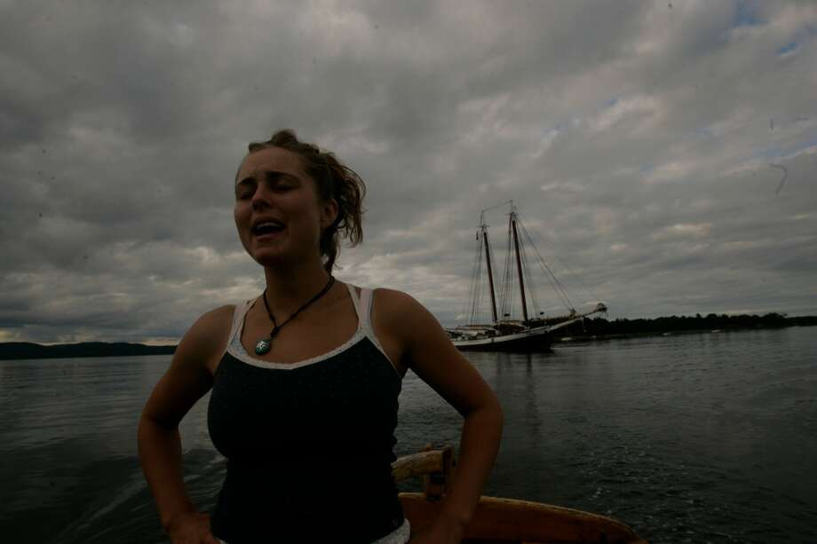 Kristi Williamson, a crew member aboard the Grace Bailey, sings a sea chanty while steering a yawl boat from the ship to Warren Island State Park.