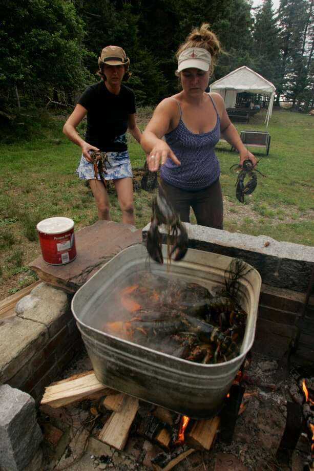 Crew members of the Grace Bailey prepare the main course during a lobster-boil dinner at Warren Island State Park in Maine's Penobscot Bay.