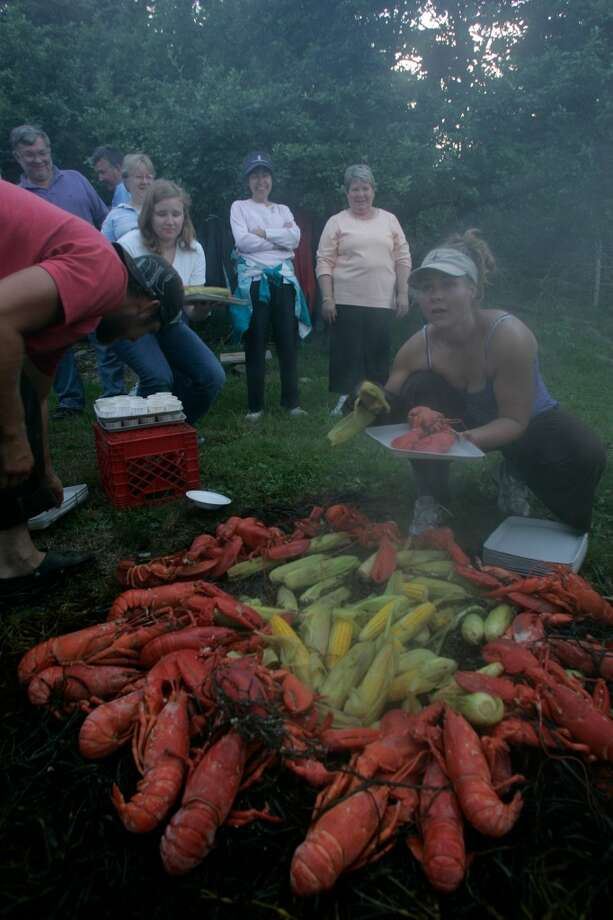 Crew members of the Grace Bailey serve up the main course during a lobster-boil dinner at Warren Island State Park in Maine's Penobscot Bay.