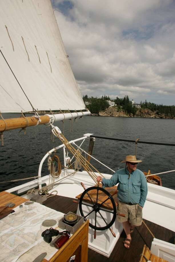 Capt. Troy Sullivan steers the Grace Bailey, an 82-foot schooner, around Penobscot Bay, Maine.